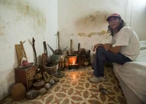 Cuba, Havana Vieja,  man sitting at Santeria Altar