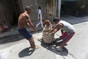Cuba, Habana Vieja, children dragging a bucket of water to their home.